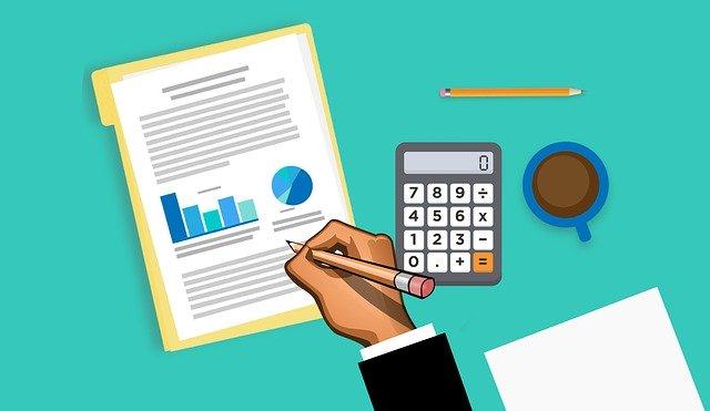 kreslený obrázek ruky píšící na papír, na kterém jsou grafy, vedle kalkulačka, hrnek s kávou, tužka a další papír.jpg