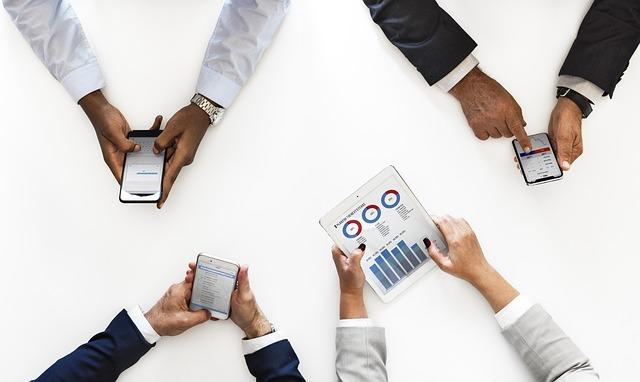 4x ruce na bílém stole, 3x drží telefon a ženské drží tablet s grafy.jpg